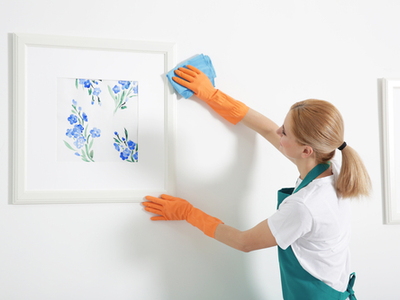 A woman carefully cleans her art for storage