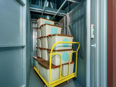 A dolly full of bins in a storage facility elevator
