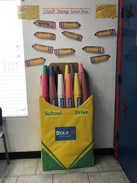 A display for the Back to School Drive at StaxUP Storage San Ysidro looks like a 4-foot-tall opened box of crayons.