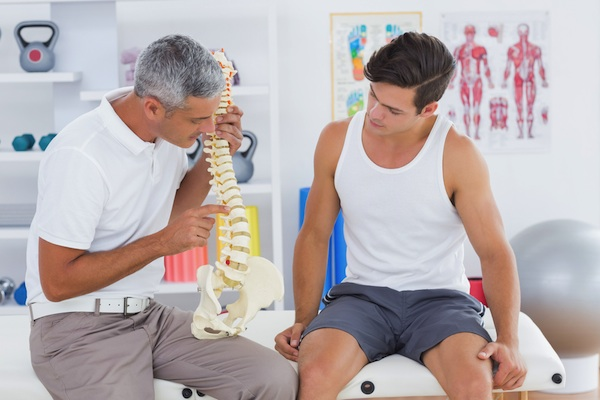 man consulting doctor about back pain