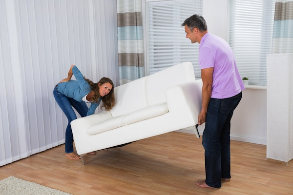 Woman gripping back in pain while moving white couch